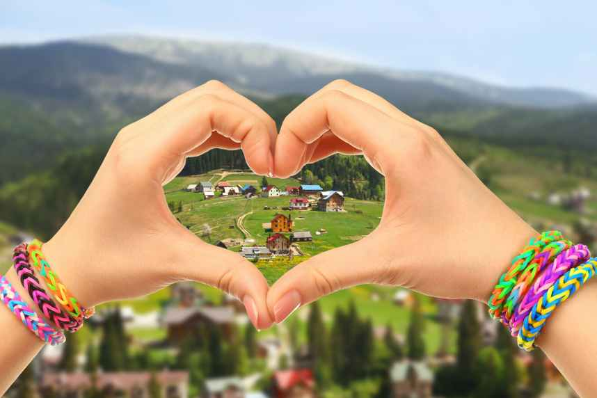 Woman holds hands in the shape of a heart on nature background