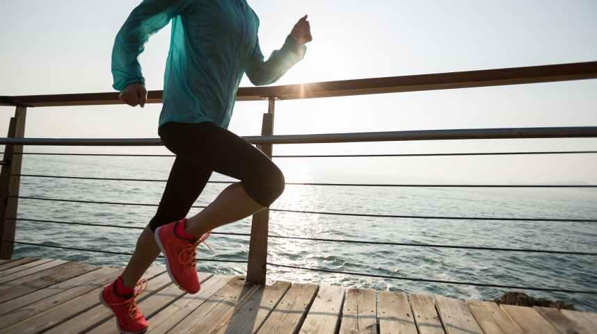 female runner running on seaside boardwalk during sunrise